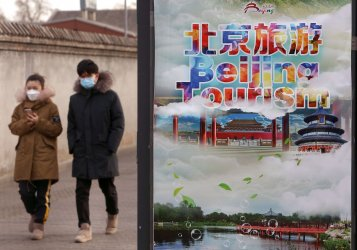 Chinese walk along a sidewalk wearing protective face masks in Beijing, China