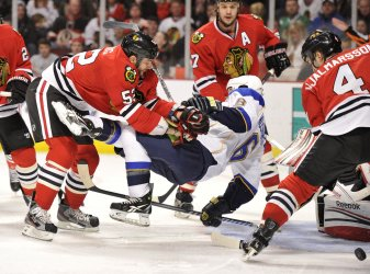 Blackhawks' Bollig checks Blues' Huskins in Chicago
