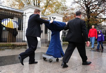 White House staff push a podium down a sidewalk Washington