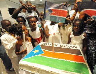 Southern Sudanese refugee children surround a cake decorated with the South Sudan flag during independence celebrations in Tel Aviv, Israel