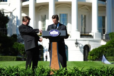 White House staff use a tape measure to adjust a podium in Washington