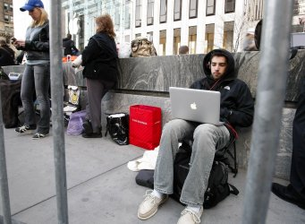 Shoppers wait in line on the eve of the April 3rd release of the new Apple iPad in New York