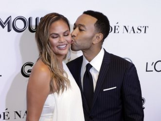 John Legend kisses his wife Chrissy Teigen as they arrive to the 2018 Glamour Women of the Year Awards