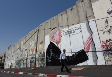 A Palestinian Walks Past Graffiti Of U.S. President Donald Trump On Separation Wall, Bethlehem