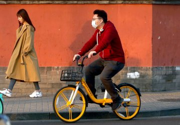A student, not wearing a face mask, visits a tourist area in Beijing, China