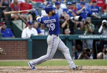Toronto Blue Jays' Jose Bautista hits a three-run home run in Arlington, Texas