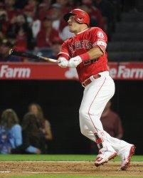 Los Angeles Angels'  Mike Trout hits a sacrifice fly ball against the Mariners in Anaheim
