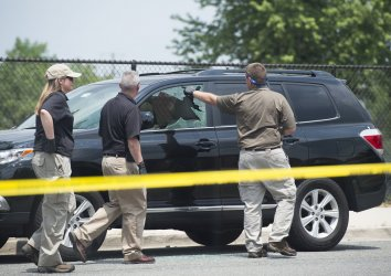 Law enforcement work the scene near Simpson Field where a gunman opened fire in Alexandria, Va.
