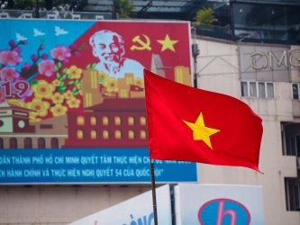 A Vietnamese Flag Waves in Front of a Billboard of Ho Chi Minh