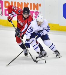 Capitals' Evgeny Kuznetsov and Maple Leafs' William Nylander fight for the puck