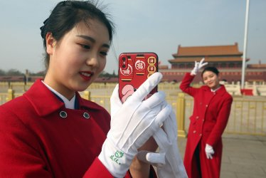 Chinese delegate hostesses take pictures during the NPC in Beijing, China