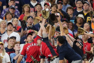 Fans field homer by Indians' Carlos Santana during the MLB All-Star Home Run Derby in Cleveland, Ohio