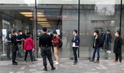 Chinese stand in line outside Apple's flagship store in Beijing, China