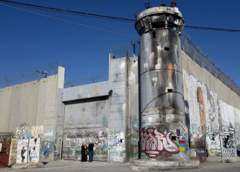 Palestinians Stand In Front Of Israel's Separation Wall In Bethlehem
