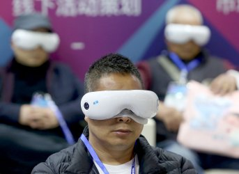 Potential buyers try on therapeutic visors at an e-commerce expo in Yiwu, China