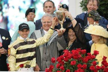 Jockey Flavien Prat and trainer Bill Mott holds up the Derby  trophy