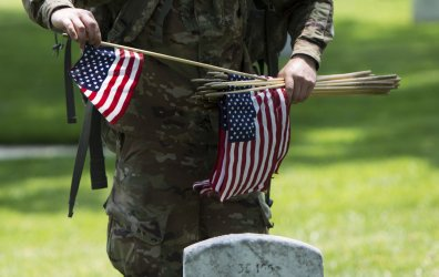 A member of the Old Guard places a flag at a grave at Arlington Cemetery