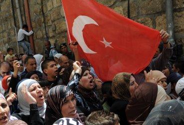 Palestinians carry a Turkish flag after Moslem Friday prayers in Jerusalem's Old City