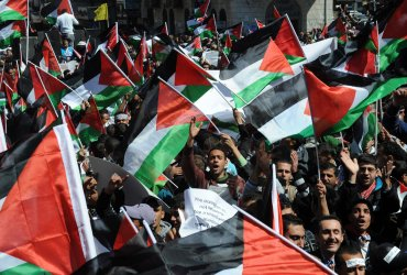 Palestinians wave flags at a rally in Ramallah, West Bank, calling for the end of divisions  between rival political factions Hamas and Fatah