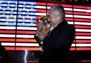 Cesar Millan stands in Times Square with a puppy from the North Shore Animal League after ringing the closing bell at the NASDAQ In New York