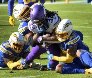 Minnesota Vikings running back Dalvin Cook is tackled by Los Angeles Chargers Thomas Davis Jr (L), Brandon Mebane (C) and Derwin James Jr