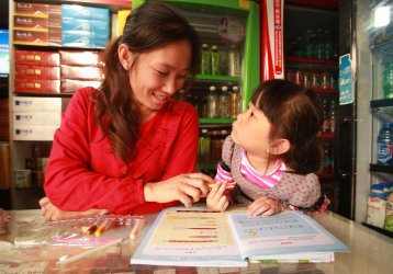 A mother helps her daughter with homework in Kunming