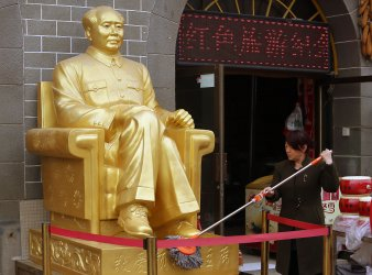 Woman cleans statue of Mao at Communist-themed souvenir shop in Yan'an, China