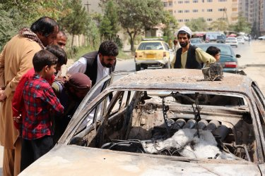 Afghans Residents Look at Vehicle Destroyed by U.S. Drone