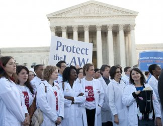 Pro health care reform supporters rally in front of the Supreme Court in Washington