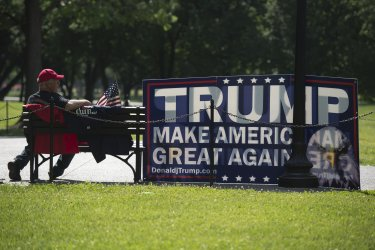 Trump supporter sits with Trump sign before Rolling Thunder rally