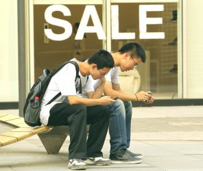 Chinese teenagers use their phones outside a mall in Beijing