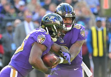 Ravens QB Lamar Jackson hands off Gus Edwards during an NFL game in Baltimore