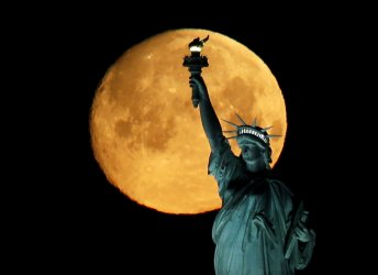 A Super Worm Moon sets behind The Statue Of Liberty