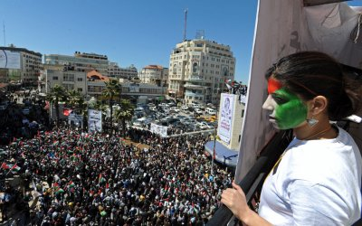 A Palestinian girl with a flag painted on her face looks down on a rally in Ramallah, West Bank, calling for the end of divisions  between rival political factions Hamas and Fatah