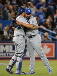 Royals Morales and Butera hug each other