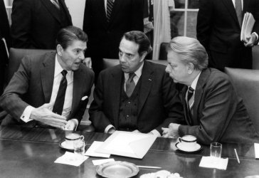 Ronald Reagan speaking with Robert Dole and Robert Byrd in the Cabinet Room at the White House.