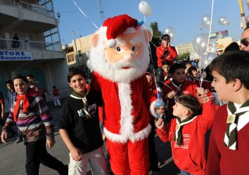 Palestinian children gather around Santa Claus during a pre-Christmas march in Bethlehem, West Bank