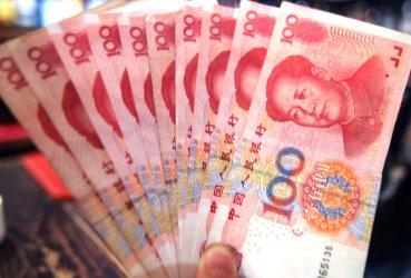Bank employee displays RMB100 in Beijing