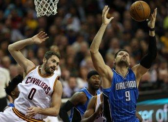 Orlando Magics' Nikola Vucevic grabs a rebound  over Cavaliers' Kevin Love