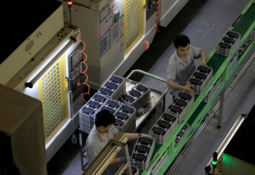 Employees work on assembly line for smartphone parts in Dongguan, China