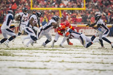 Chiefs' Tyreek Hill is tackled by several Broncos