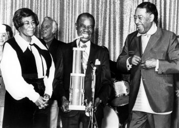Louis Armstrong receiving a trophy from Ella Fitzgerald and Duke Ellington.