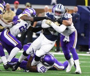 Dallas Cowboys running back Ezekiel Elliott (21) gets wrapped up by several Vikings