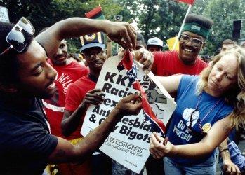 Demonstrators protesting a Ku Klux Klan march burn a Confederate flag