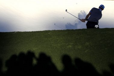 Patrons watch Martin Kaymer hit out of a bunker at the Masters