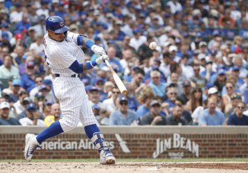 Cubs Javier Baez hits a triple against the Brewers in Chicago