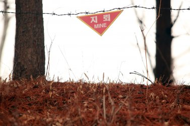 A mine field warning sign hangs in the DMZ