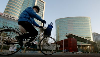Womman Cycles Past CNOOC Headquarters in Beijing, China