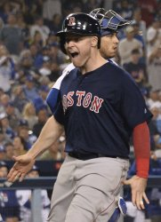 Red Sox Holt celebrates scoring during the thirteenth inning in Game 3 of the World Series