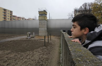 A memorial service is held at a segment of the original Berlin Wall